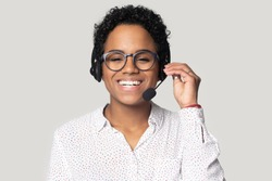 Headshot portrait of smiling african American female call center agent in glasses wearing headset with microphone, happy biracial girl dispatcher in earphones laugh isolated on grey studio background