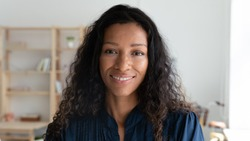 Headshot portrait of smiling african American female employee look at camera posing in modern office, happy biracial young businesswoman show confidence and motivation, work leadership concept