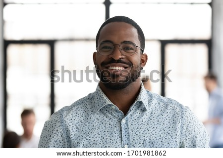 Headshot portrait of smiling African American male employee in glasses look at camera posing at workplace, happy motivated biracial man worker show confidence and leadership, employment concept