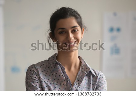 Headshot portrait of smiling attractive indian female employee look at camera making picture in office, happy positive ethnic woman beautiful millennial worker posing for photo at workplace