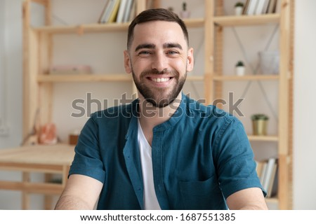Headshot portrait of smiling Caucasian young male employee look at camera posing at workplace, happy European businessman show confidence and motivation for future career success, leadership concept