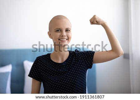 Headshot portrait of smiling young Caucasian hairless woman sick with cancer show power strength beat disease. Happy millennial female battle oncology, overjoyed about remission or recovery. Stock photo ©