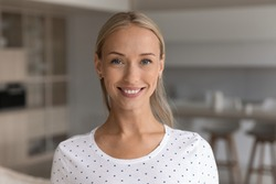 Headshot portrait of smiling young 20s Caucasian woman renter or tenant pose in living room in new home. Close up profile picture of happy millennial female in own house. Rental, employment concept.