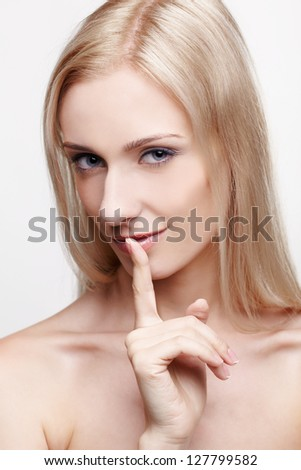 headshot portrait of young beautiful blonde woman asking to be quiet
