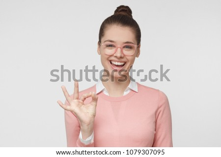 Headshot portrait of young beautiful Caucasian female pictured isolated on gray background dressed in bright casual clothes, laughing happily while making OK sign with fingers with relaxed look