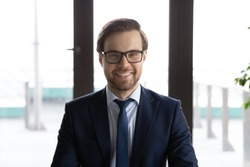 Headshot portrait of young Caucasian male director or boss in glasses posing at workplace, profile picture of happy confident businessman in formal suit show motivation and leadership qualities