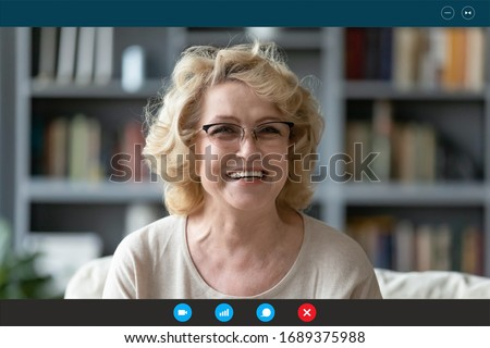 Headshot portrait screen application view of smiling elderly woman sit on couch at home have online Webcam conversation with relatives, happy mature grandmother talk speak on video call on quarantine