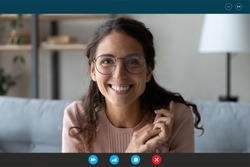 Headshot portrait screen view of smiling millennial woman in glasses sit on couch at home talk on video call with relatives, happy young female have Webcam conversation, take online course indoors