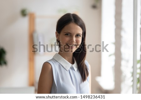 Headshot profile picture of confident young woman bank specialist or coach stand looking smiling at camera, happy positive millennial female employee or worker posing making photo, shooting for album