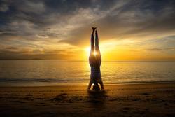 Headstand, Sunset yoga woman on sea coast