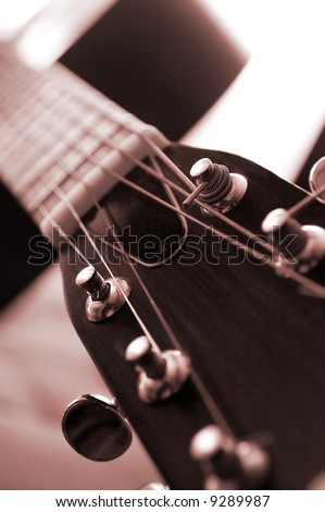 Headstock and tuners of an acoustic guitar close up