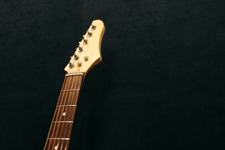 Headstock of the six string electric guitar top view in sound recording studio. Headstock of electric guitar  flat lay on black background. Musical instrument closeup with free space.