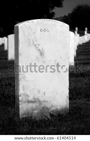 Headstone in a graveyard with evil 666 engraving