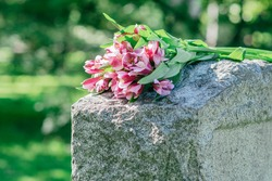 Headstone in cemetery with flowers for concept of death and loss