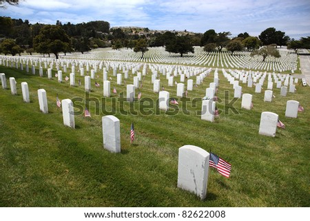 Headstones and American Flags and floral display at an American National Military Cemetery