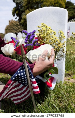 Headstones, person placing floral arrangement, and Flags at National Military Cemetery