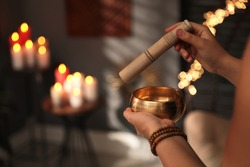 Healer using singing bowl in dark room, closeup