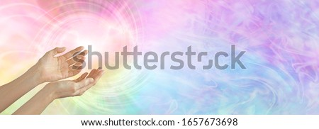 Photo of  Healer working with colour healing full spectrum energy  - female cupped hands sensing  rainbow coloured vortex with  copy space