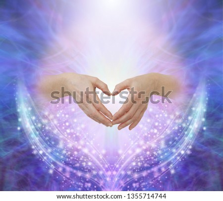 Healers hands making a humble heart shape - female hands forming a heart shape against a pink circle surrounded by ethereal blue and beautiful glittering sparkles with copy space above