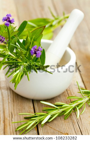Healing herbs in white ceramic mortar and pestle