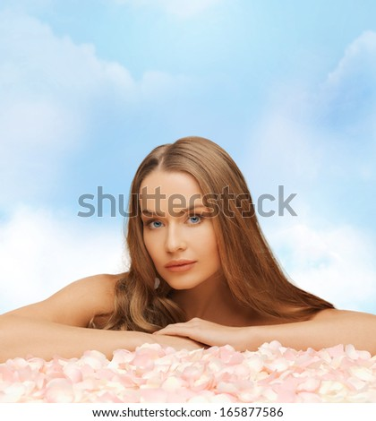 health and beauty concept - beautiful woman with long hair and rose petals