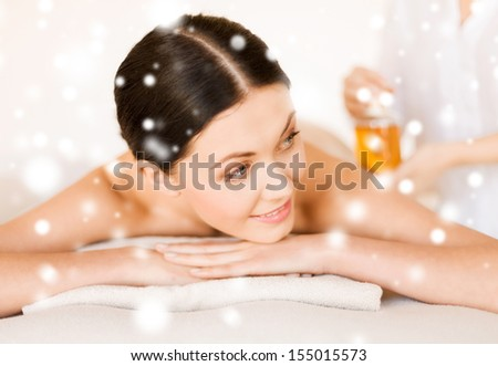 health and beauty concept - woman in spa salon getting oil treatment