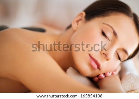health and beauty, resort and relaxation concept - beautiful woman with closed eyes in spa salon with hot stones