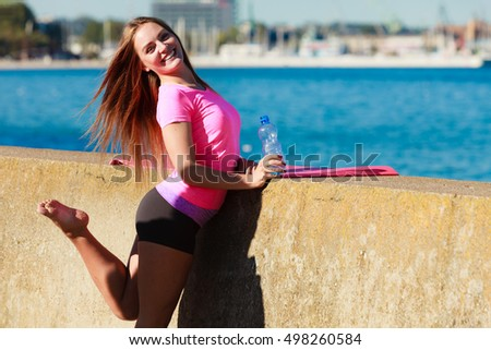Health and body care idea. Sporty fit attractive woman with bottle of water after exercising workout outdoor. #498260584
