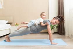 Health and fit concept. Young beautiful pregnant asian woman doing fitness exercise in the domestic room with her little kid son together. FItness materinity and motherhood