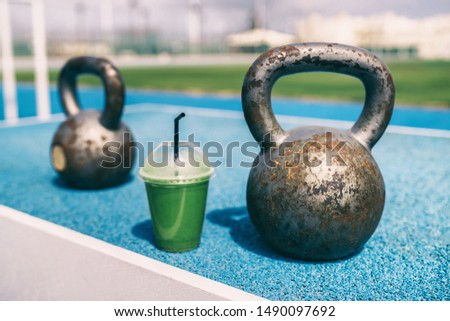 Health and fitness green smoothie detox drink at gym with kettlebells weights at outdoor training fitness center. Plastic cup of vegetable juice morning breakfast next to kettlebell weight equipment.