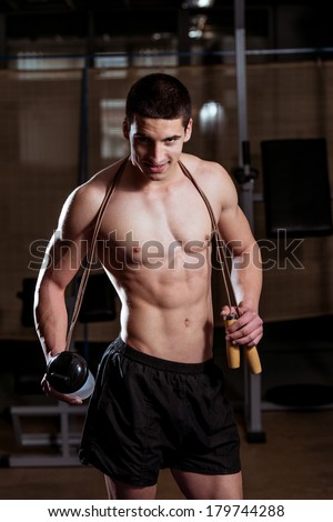 Health and Fitness - Handsome Muscular Man With Jumping Rope - Holding A Bottle Of Water In His Hand