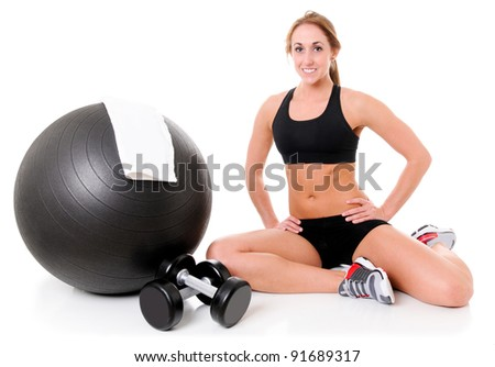 Health and Fitness woman in gym outfit with a Pilates ball, towel and weights