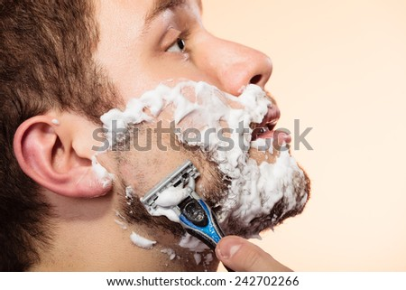 Health beauty and skin care concept. Closeup young bearded man with foam on face shaving on bright orange background.