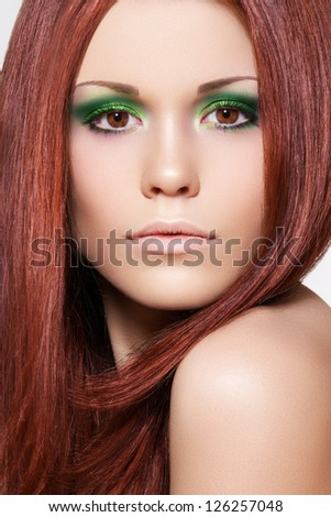 Health, beauty, wellness, haircare, cosmetics and make-up. Beautiful fashion hairstyle. Woman model with shiny straight long red hair and vibrant green make-up