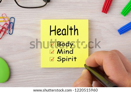 Health Body Mind Spirit handwriting on note with marker pen and glasses. Health concept.