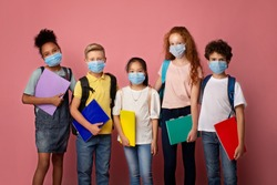 Health care and education concept. Portrait of schoolchildren wearing protective masks against pink background