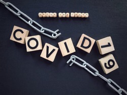 Health care and social issues concept. BREAK THE CHAIN and COVID 19 written on wooden blocks.