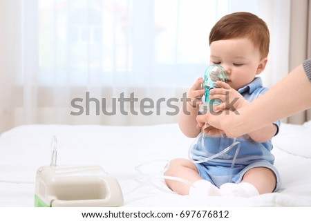 Health care concept. Woman with little baby and nebulizer indoors #697676812
