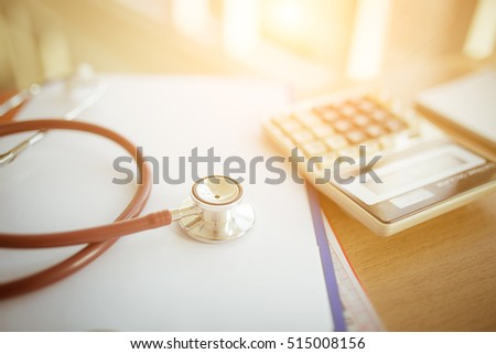 Health care costs concept picture : Selective focus Stethoscope and calculator on a medical chart ,symbol for health care costs or medical insurance with effect light added.