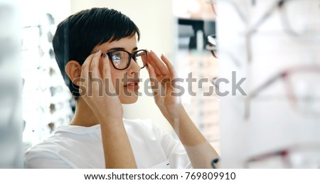 health care, eyesight and vision concept - happy woman choosing glasses at optics store #769809910