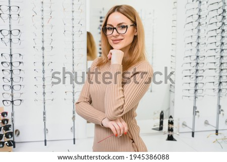 Health care, eyesight and vision concept - happy woman choosing glasses at optics store. Portrait of beautiful young woman trying new glasses in optician store Foto stock ©