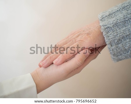 Health care for elderly person, Parkinson's disease, Alzheimer's disease, dementia and disability person. Close up of young doctor/caregiver hands holding senior patient hands for helping/supporting.