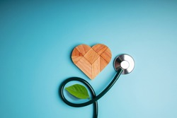 Health Care, Harmony and Organic Healthy Lifestyle Concept. Living and Close to Nature. Wooden Jigsaw as Heart Shape with Stethoscope and Leaf. Look like Flower Plant. Growth of Love and Relationship