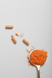 health care lifestyle concept. spoon with turmeric powder and pills on blue background. flat lay top view copy space