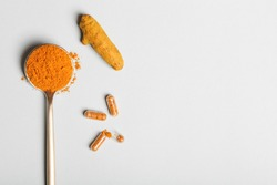 health care lifestyle concept. spoon with turmeric powder, root and pills on blue background. flat lay top view copy space
