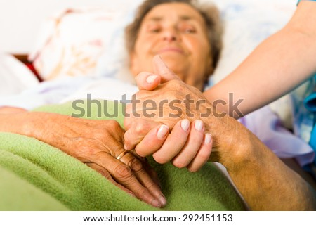 Health care nurse holding elderly lady\'s hand with caring attitude.