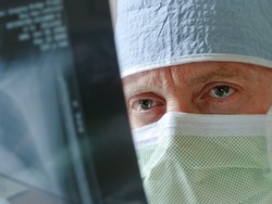 Health care professional  intensely studies x-ray results prior to surgery. Selective focus on eyes.  Would make good hospital, physician, doctor, surgeon illustration. Photographer as model.