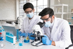Health care researchers working in life science laboratory. Male research scientist and supervisor preparing and analyzing microscope slides in research lab. The invention of the coronavirus vaccine.