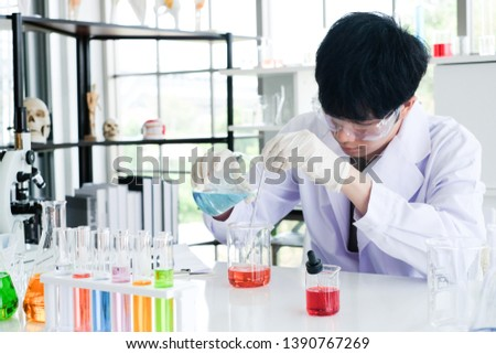 Health care researchers working in life science laboratory. Young male research scientist  preparing and analyzing slides in research lab.