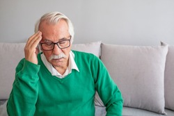 Health care, stress, old age and people concept - Senior man suffering from headache at home. Old man suffering from headache. A Distraught Senior Man Suffering From a Migraine